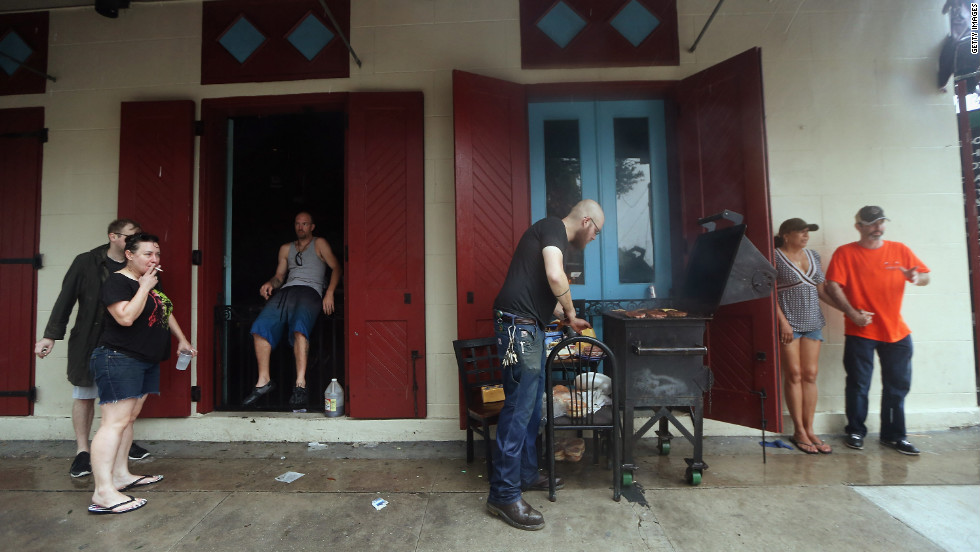 People gather beneath an awning for an impromptu cookout at a bar that lost electricity during Hurricane Isaac in New Orleans.