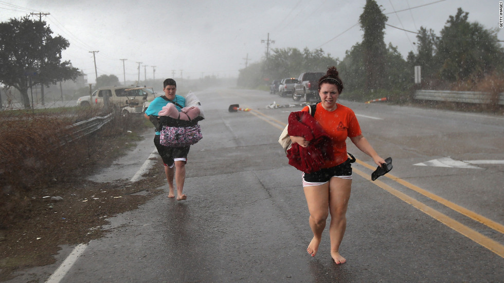 Residents run down a road in Slidell clutching their belongings as they evacuate an area of rising floodwaters from Isaac's rains.
