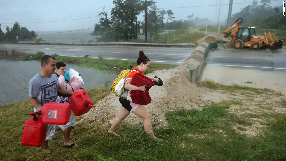 Residents carry pillows, blankets and fuel containers past a flood berm while evacuating an area of rising floodwaters on Thursday in Slidell.