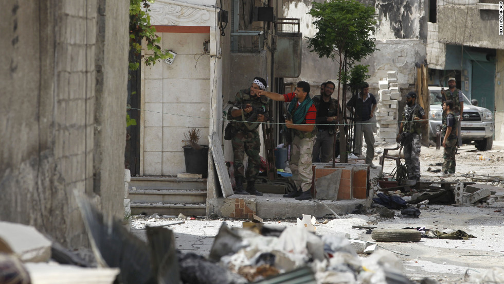 Free Syrian Army fighters take up position during clashes in the El Amreeyeh neighborhood of Aleppo.