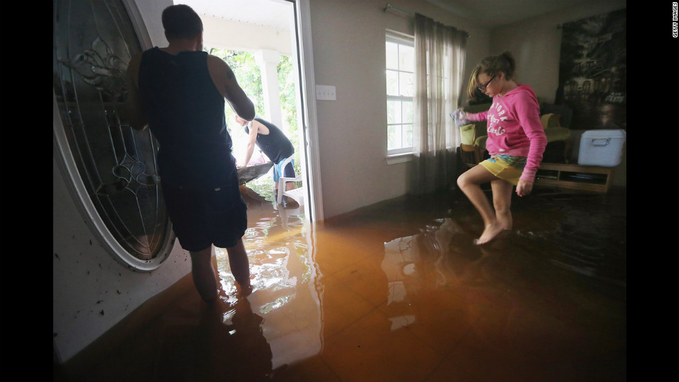 Brittany Trumbaturi, right, prepares to leave her flooded home with family member Joshua Barbot, center, who came to rescue family members in a boat. Officials warned of continued threats from storm surges and flooding as Isaac moved inland.