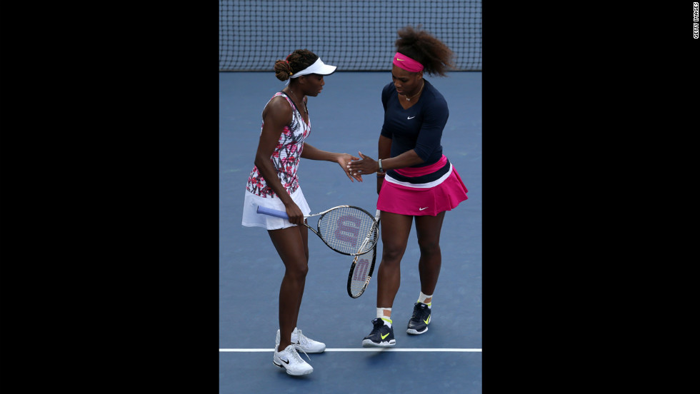 Venus Williams, left, and Serena Williams tap hands during their women's doubles first-round match.