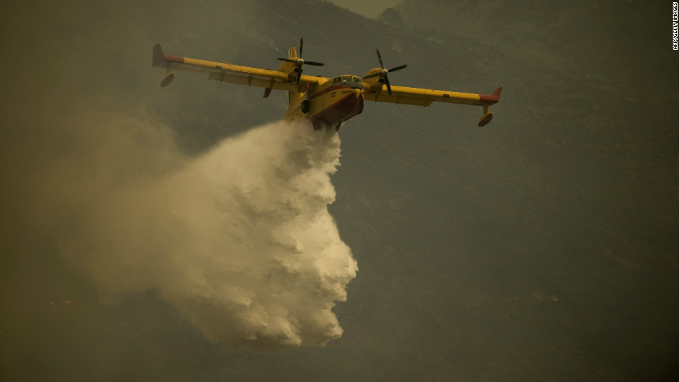 A fire brigade plane pours water to extinguish a wildfire in Ojen on August 31, 2012.