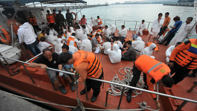 Asylum seeker survivors are seen on board an Indonesian rescue boat at Merak seaport on August 31, 2012.