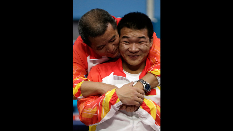 Chinese Qi Feng is congratulated by his coach Weipo Li for his gold during the medal ceremony of the Men's -52 kg powerlifting.