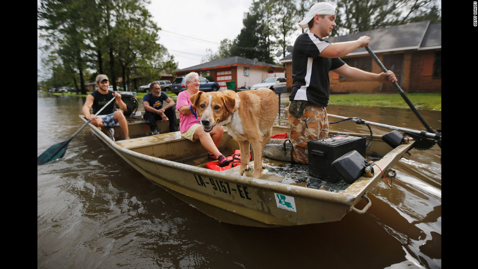 Jewel Rico and her dog Chico are rescued from flood waters from Isaac on Thursday, August 30, in Reserve, Louisiana.