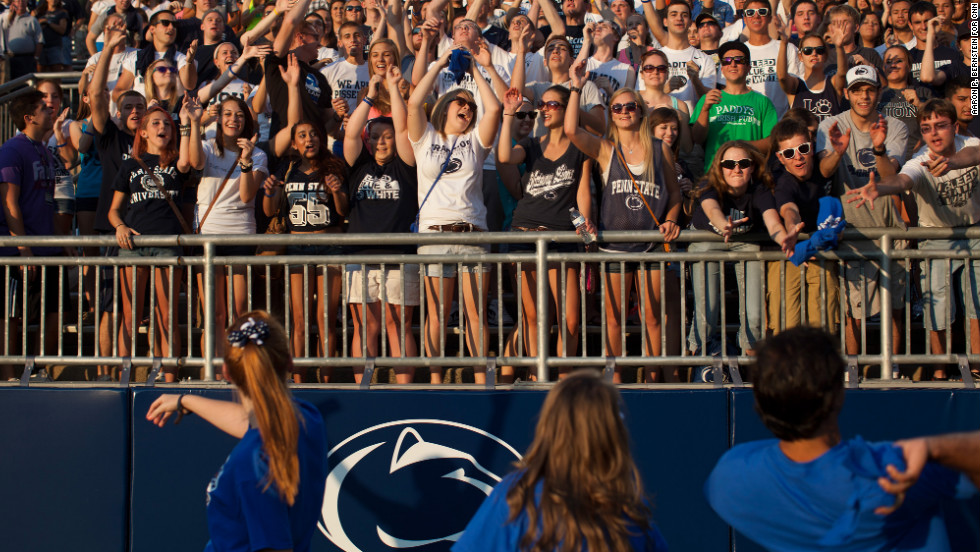 Penn State football fans grab for T-shirts thrown into the stands at Beaver Stadium.