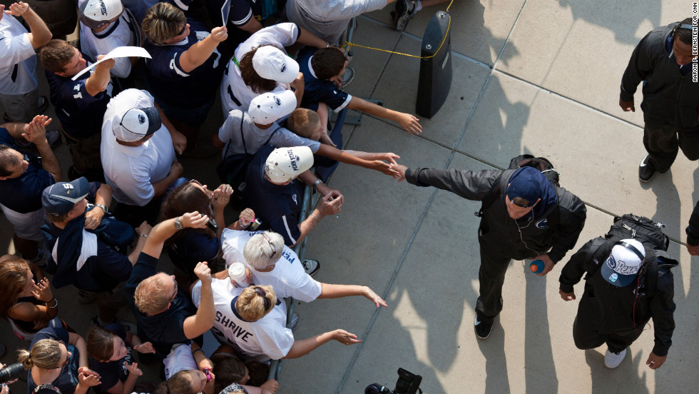 Penn State fans greet members of the football team as they arrive at the stadium.