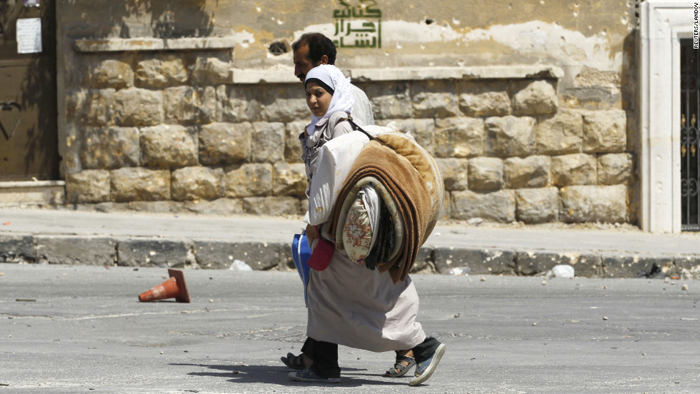 Civilians carry their belongings and flee the El Edaa district after an airstrike.
