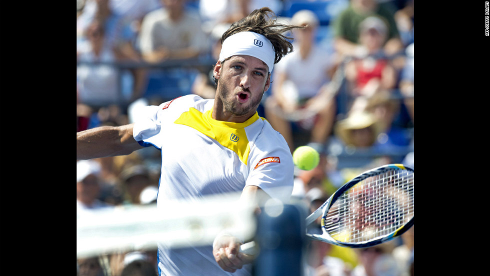 Spain's Feliciano Lopez of Spain hits a return to Andy Murray of Great Britain.
