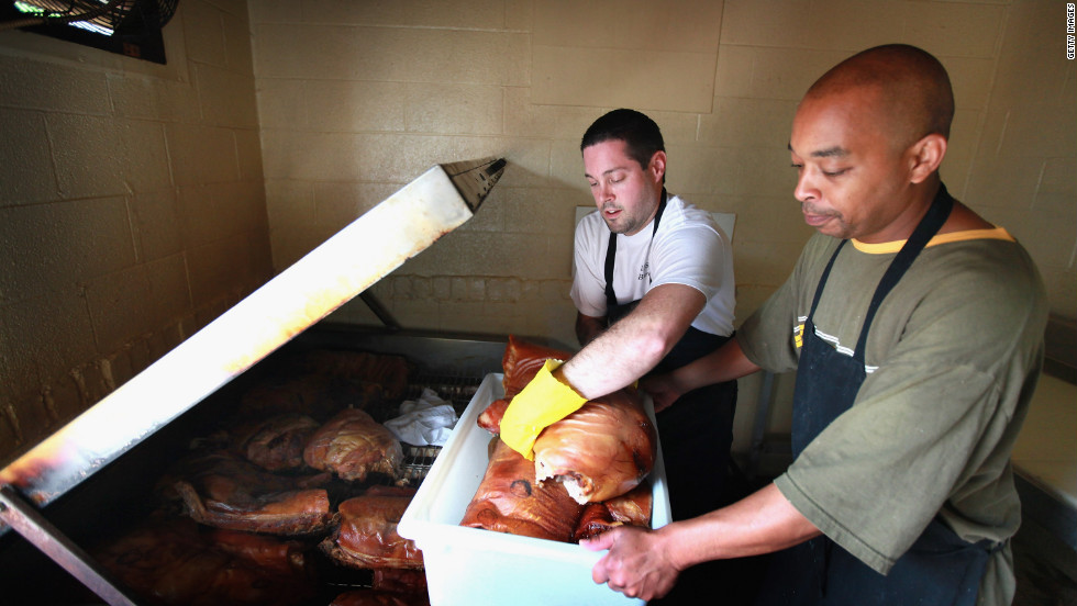 Bill Spoon's BBQ employees remove pork from a smoker at the nearly 50-year-old restaurant known for its Eastern North Carolina Style BBQ. The restaurant was recently recovnized as one of the 10 best BBQ restaurants in the United States. The state is expecting $150 million to $200 million economic impact from the DNC.