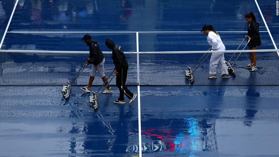A grounds crew dries the court Tuesday after rain suspended play.