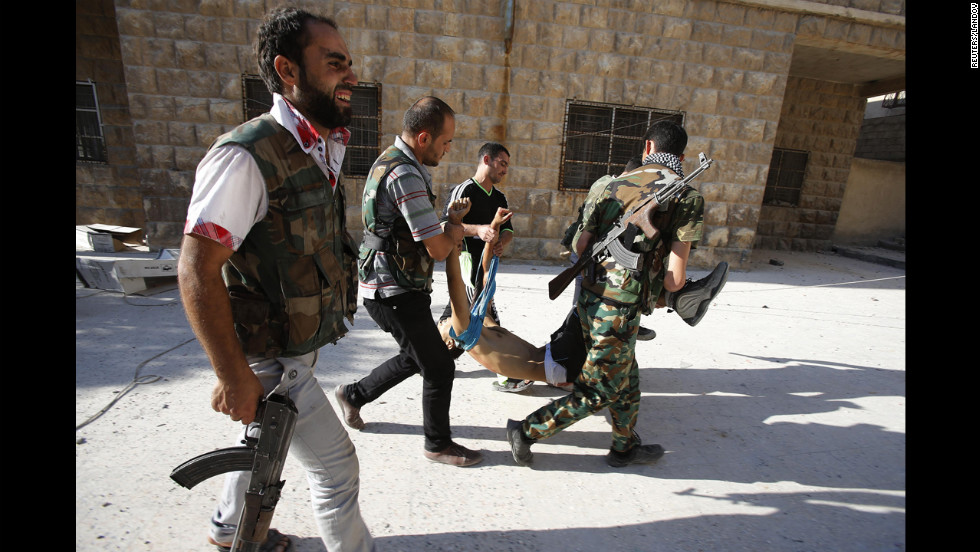 Rebels carry the body of a fellow fighter after a sniper shot him in Aleppo on Tuesday, September 4.