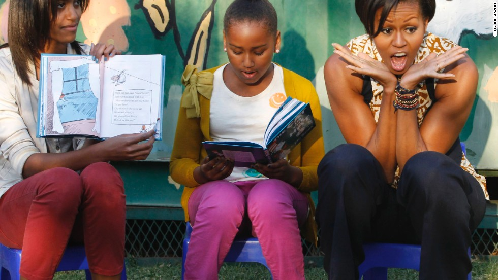 "First lady Michelle Obama with Sasha and Malia Obama, reading to children from ""The Cat in the Hat"" by Dr. Seuss as they visit the Emthonjeni Community Centre in Zandspruit Township, Johannesburg, South Africa, on June 21, 2011."
