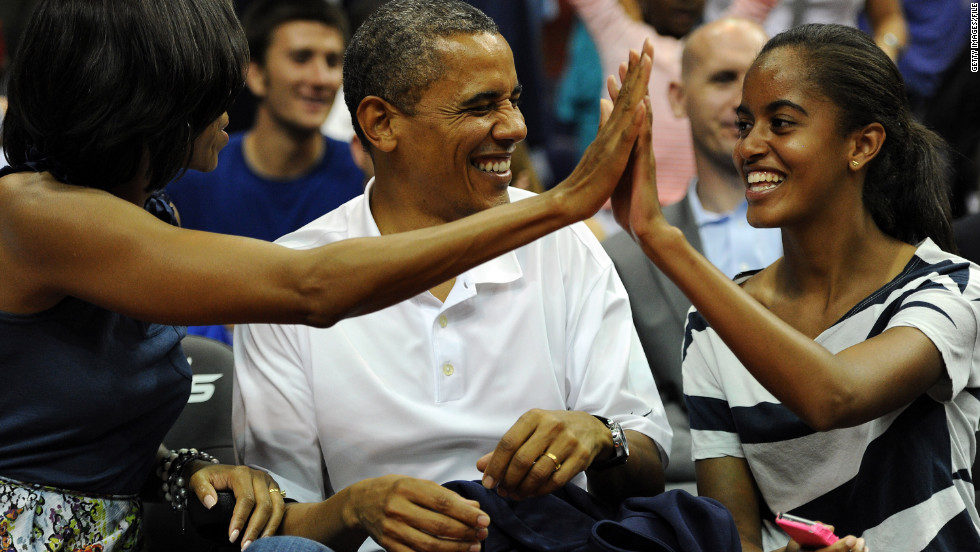 President Obama shares a laugh with his wife, Michelle, and daughter Malia, as the U.S. Senior Men's National Team plays Brazil in a pre-Olympic exhibition basketball game on July 16, 2012, in Washington.
