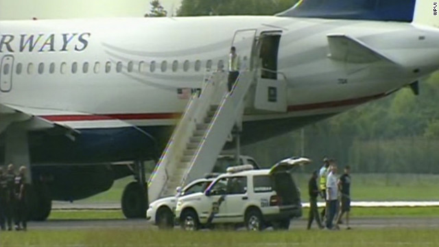 A US Airways plane bound for Dallas was diverted to Philadelphia, and a passenger was removed in handcuffs.