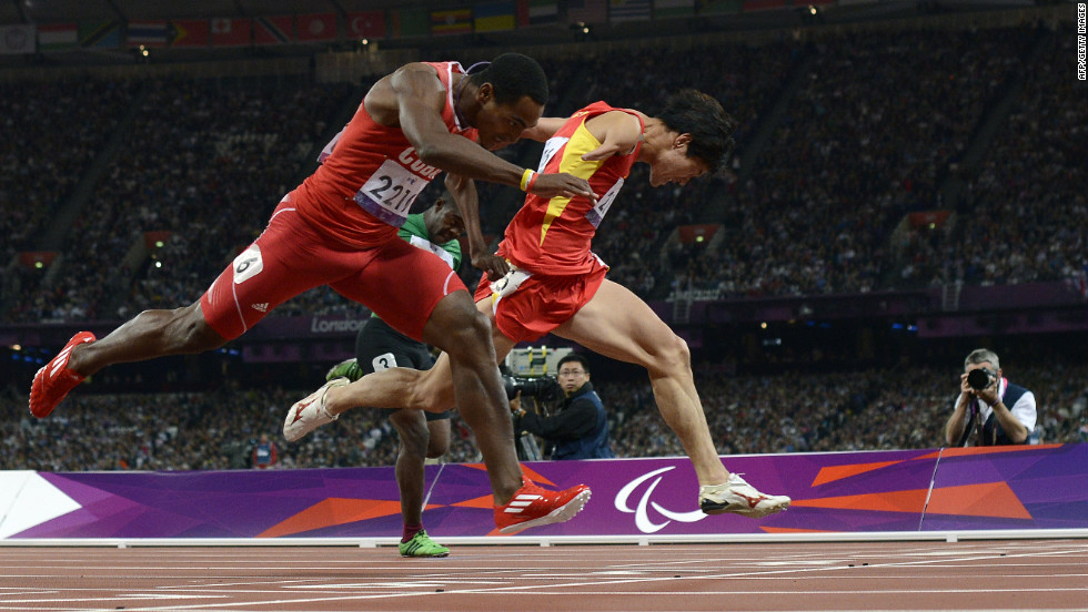 China's Zhao Xu, right, dips for the finish line, just ahead of Cuba's Raciel Gonzalez Isidoria to win the men's 100-meter T46 final on Thursday, September 6.