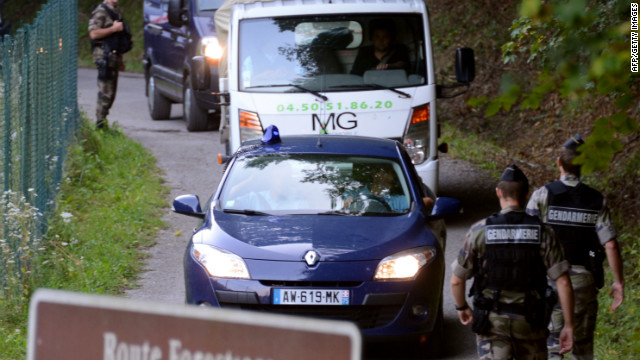 A tow truck escorted by French gendarmes on the 'Combe d'Ire' road carries the car in which three people were shot dead on September 6, 2012 in the French Alpine village of Chevaline. A four-year-old girl spent hours curled up under her mother's body and miraculously survived the deadly attack that left her father, mother and grandmother dead and her elder sister seriously injured, officials said