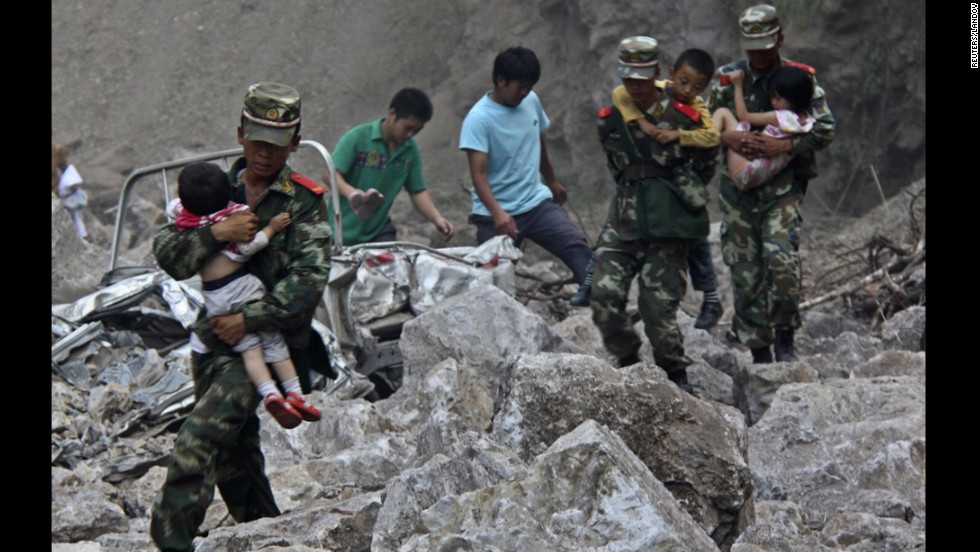 Soldiers carry children to safe ground after two earthquakes hit Zhaotong, Yunnan province, on Friday, September 7.