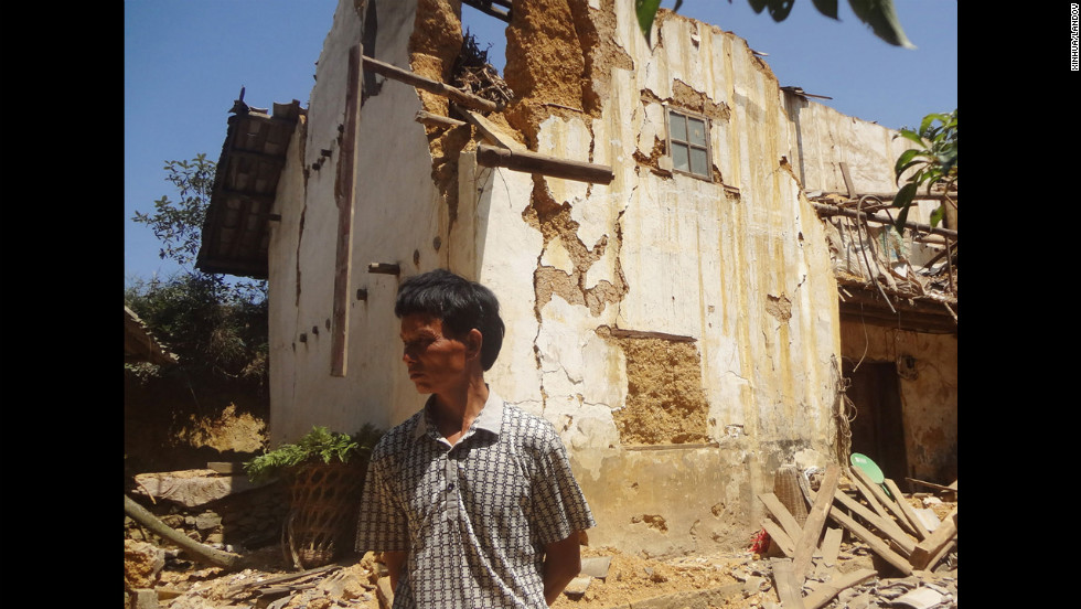 A man stands in front of a damaged house in Xinlong Village of Weining County, in Guizhou province.