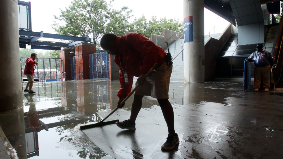 Grounds crew workers clear water during a rain delay on Saturday.