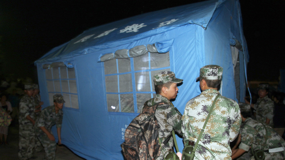 Rescuers set up a tent at an emergency relief center in Yiliang.