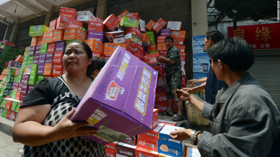 Residents receive food aid in Yiliang on Sunday. About 100,000 people have been evacuated and 100,000 others are in need of relocation, state media reported.