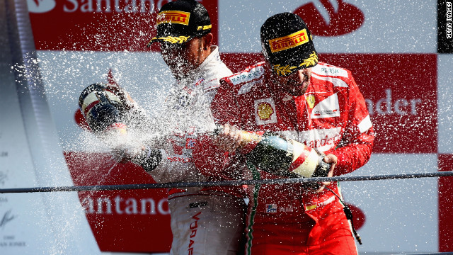 Race winner Lewis Hamilton (L) and championship leader Fernando Alonso celebrate on the podium at Monza.
