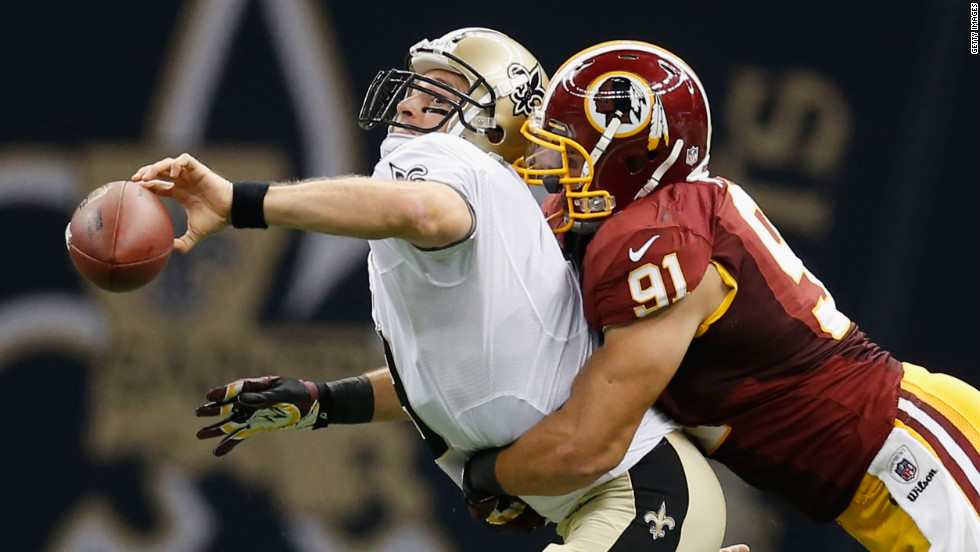 No. 9 quarterback Drew Brees of the New Orleans Saints throws the ball as he is tackled by No. 91 Ryan Kerrigan of the Washington Redskins on Sunday.