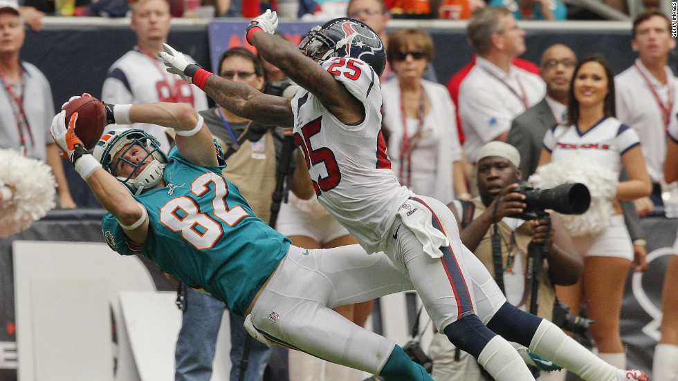 No. 82 Brian Hartline of the Miami Dolphins completes a reception as he beats No. 25 Kareem Jackson of the Houston Texans on Sunday.