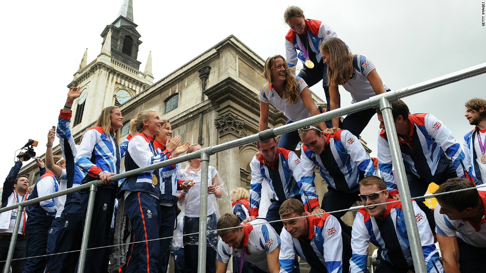 Members of the Olympics rowing team create a pyramid atop one of the floats.