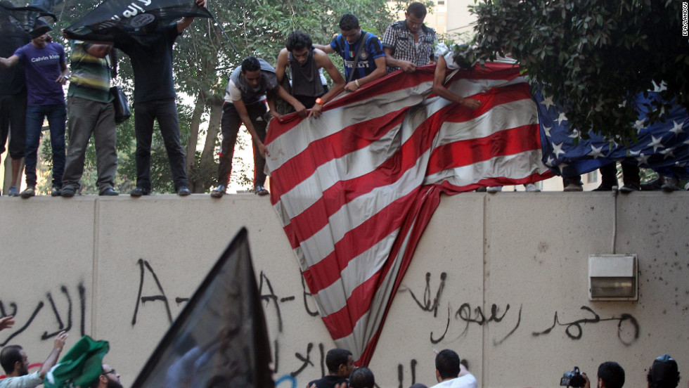 Protesters pull down a U.S. flag.