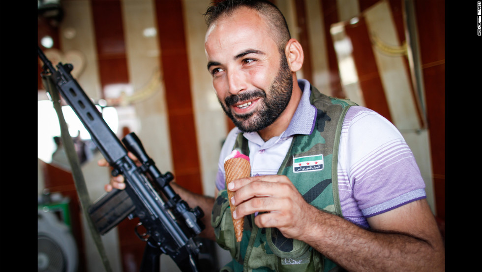 A member of the Free Syrian Army enjoys an ice cream on the road from Azaz to Aleppo on Monday.