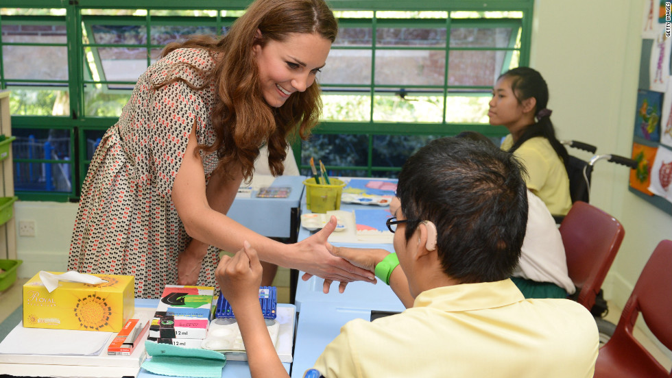 Catherine greets a child during a visit to The Rainbow Centre, a children's learning center, on Wednesday.