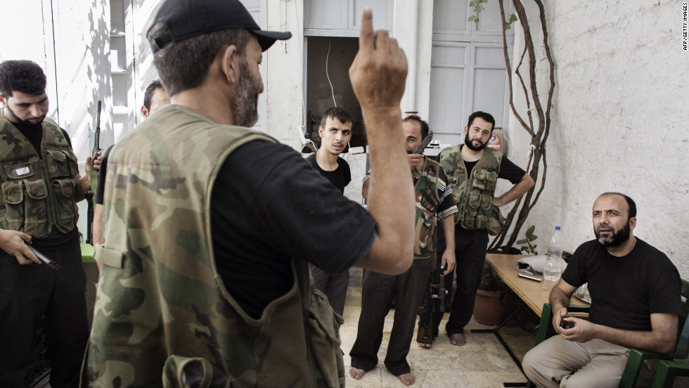 Syrian rebel commander Abu Mohammed, far right, listens to reports from fellow fighters at his base in the Old City neighborhood of Aleppo on Wednesday.