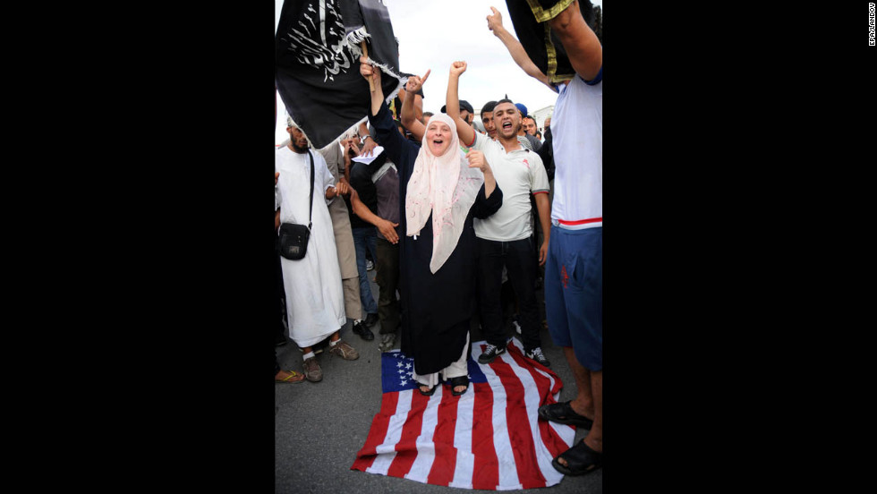 A demonstrator walks on a U.S. flag during a Wednesday's demonstration at the U.S. Embassy in Tunis.