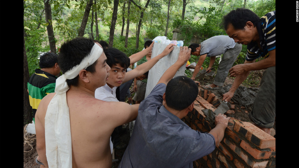 Villagers prepare a grave on Monday for an elderly man killed in Yiliang.