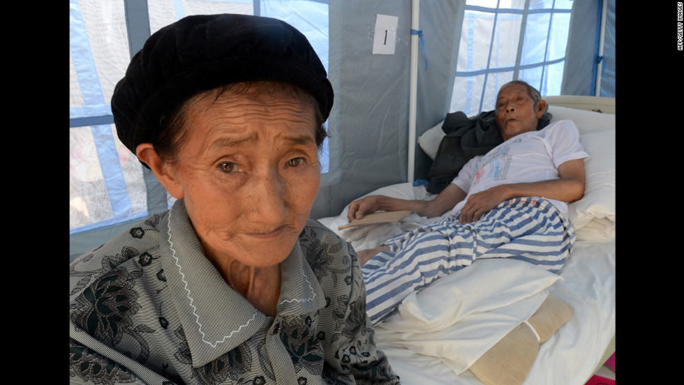 Sheng Xianqui, right, is tended by his wife at the Yiliang People's Hospital on Monday.