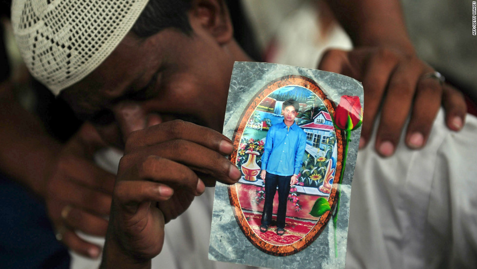 Aziz Ahmed, the father of factory worker Asif Aziz who was killed in a blaze in Karachi Wednesday, September 12, 2012, holds his son's photo as he mourns his death.