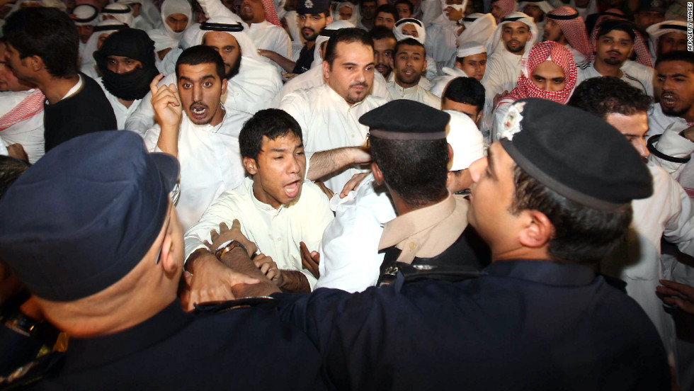 Kuwaiti police stand guard as hundreds of demonstrators protest near the U.S. Embassy in Kuwait City on Thursday.