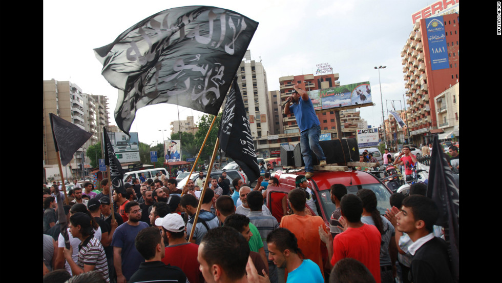 "Protesters carry flags that read ""There is no God but Allah, Mohammed is Allah's messenger"" and chant during a protest in Tripoli, Lebanon, on Thursday."