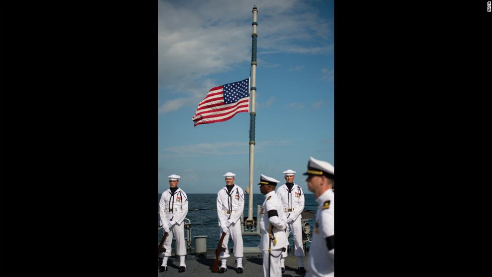 The American flag on the ship is seen at half-mast.