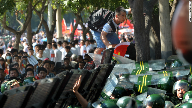 A protester (top) attempts to climb over a security barrier during an anti-Japanese protest outside the Japanese embassy in Beijing on September 15, 2012.