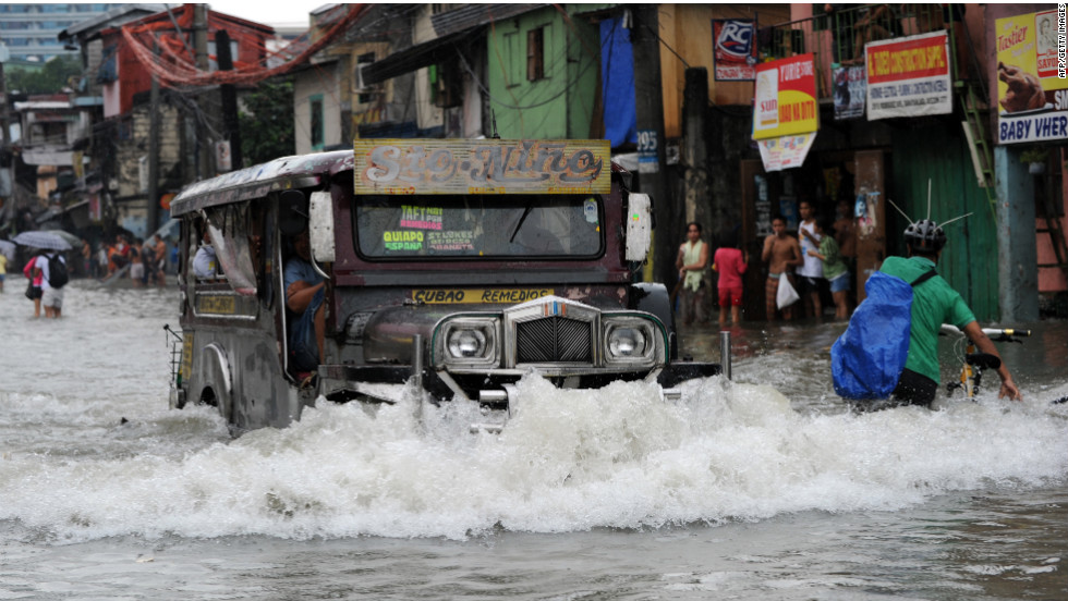 A jeepney pushes through a flooded street in Manila on Saturday.