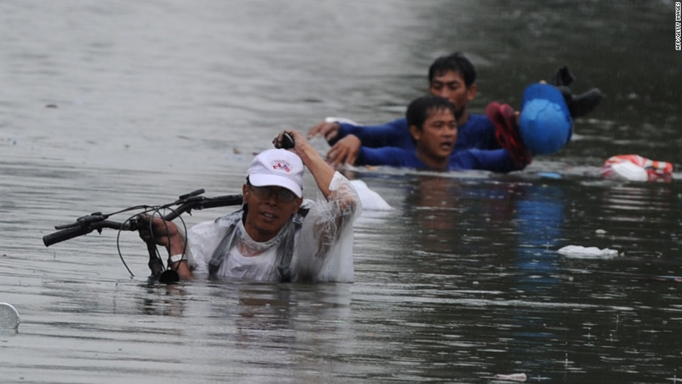 People try to hold onto their personal belongings as they wade along a flooded street in Manila.