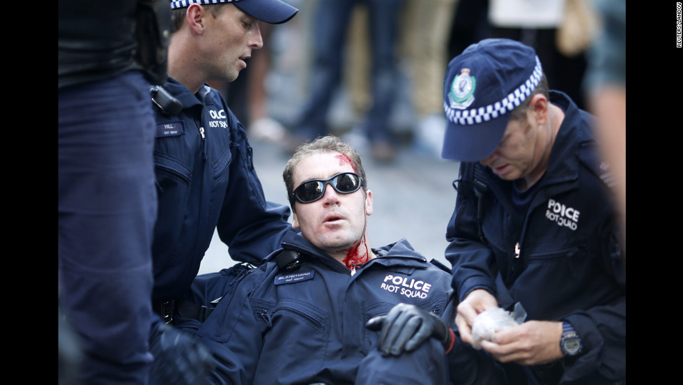 A policeman, injured by protesters, is assisted by colleagues in central Sydney on Saturday.
