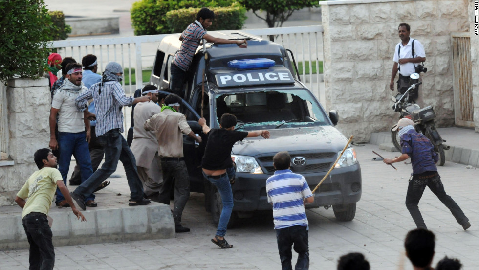 Protesters attack a police van outside the U.S. Consulate in Karachi on Sunday.