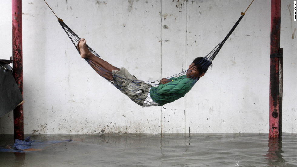 A worker sleeps on a hammock above a flooded street during a heavy downpour brought by Typhoon Sanba in Quezon City, Philippines, on Saturday, September 15.