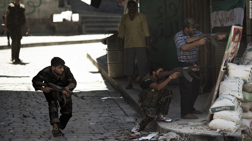 Syrian rebels prepare to fire during clashes with regime forces as they stand near a picture of Syrian President Bashar al-Assad used as a mock sniper target in Aleppo on Friday, September 14.