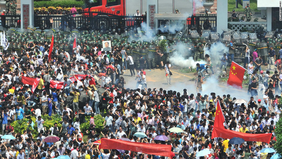 Police fire tear gas to disperse the crowds in Shenzhen, south China's Guangdong province.